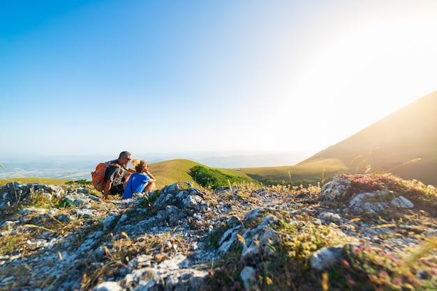 Мужчина и женщина, походы в горы региона умбрия, монте-кукко, аппеннино, италия. пара вместе смотреть закат на вершине горы. летние мероприятия на свежем воздухе.