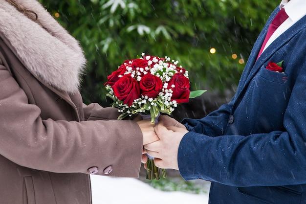 남자와 여자는 주홍 장미와 함께 아름다운 꽃다발을 들고 있습니다. 고품질 사진