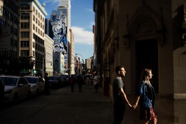 남자와 여자는 서로 아침 뉴욕에서 길을 걷고 부드러운 손을 잡고