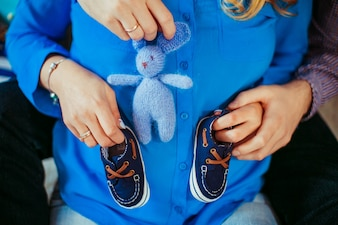 Man and woman hold tiny shoes and toys on pregnant belly