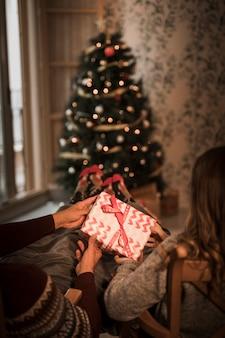 Мужчина и женщина, держащая подарочную коробку на стульях возле елки