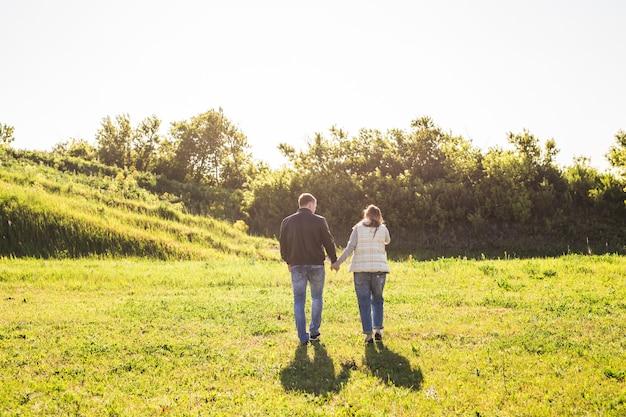 남자와 여자 손을 잡고 자연 뒷모습을 걷고