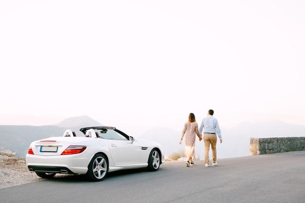 Мужчина и женщина, держась за руки, идут по дороге