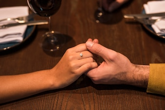 Man and woman holding hands at table with plates and glasses of wine in restaurant