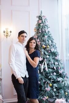 Мужчина и женщина, взявшись за руки возле елки и камина в рождественской атмосфере.