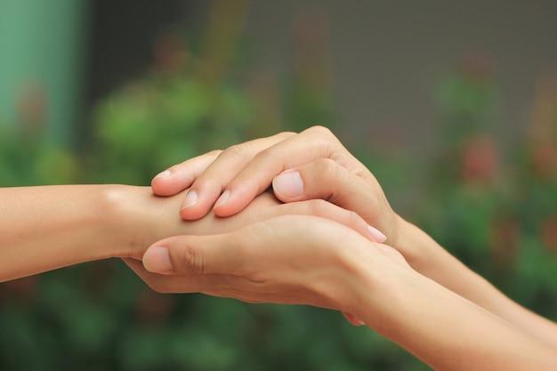 男と女の愛のロマンチックなカップルの手を繋いでいます。