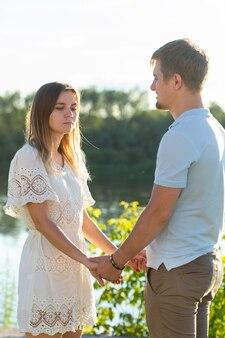 Мужчина и женщина, взявшись за руки на летней природе. пара в романтических объятиях