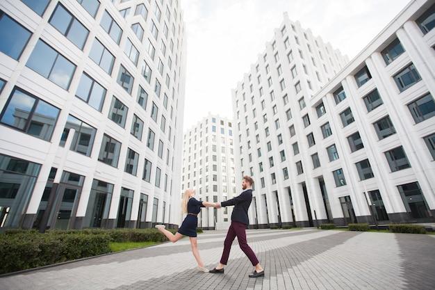 Мужчина и женщина, взявшись за руки на фоне здания бизнес-центра.