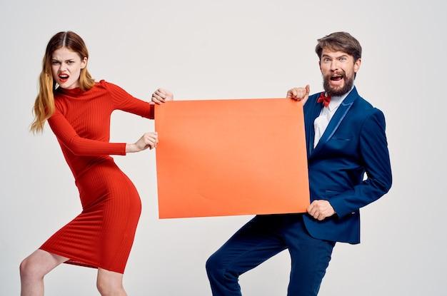 赤いモックアップコピースペース広告ポスターを保持している男性と女性
