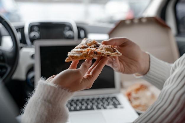 自動車でピザのスライスを保持している男性と女性。食べ物とカップルの手のクローズアップ。車のキャビンでのカップルのリラクゼーション。一緒に時間を楽しむというコンセプト