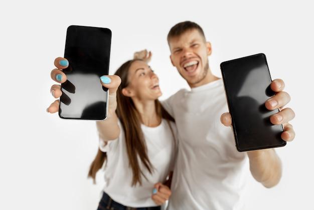 スマートフォンを持って画面を表示している男性と女性。