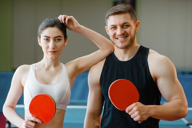 남자와 여자는 실내 탁구 라켓을 보유하고 있습니다. 스포츠에서 몇 체육관에서 탁구를 재생합니다. 테이블 테니스 클럽의 남녀 명
