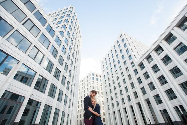 Мужчина и женщина обнимаются на заднем плане - здание бизнес-центра.