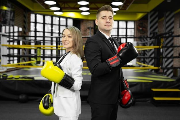남자와 여자는 양복과 권투 장갑을 끼고 서로 등을 대고 링 앞에 서 있습니다.