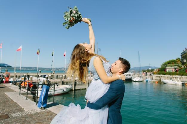 Мужчина и женщина в синей свадебной одежде возле лодок на озере гарда. влюбленная пара на скамье подсудимых. мальчик и девочка на лодке. пара гуляет по пирсу. свадебные путешествия. озеро гарда, сирмионе