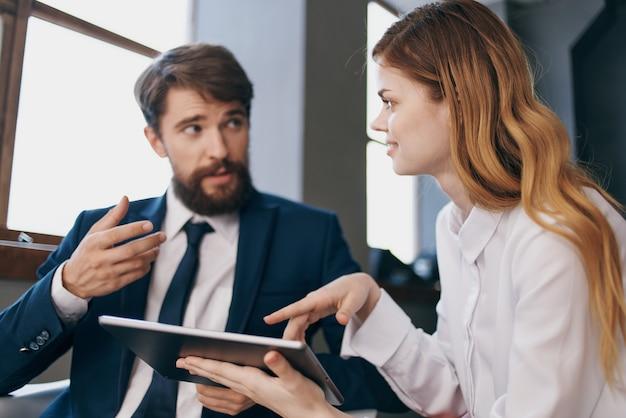 Мужчина и женщина в деловых костюмах, глядя на офис планшетных технологий