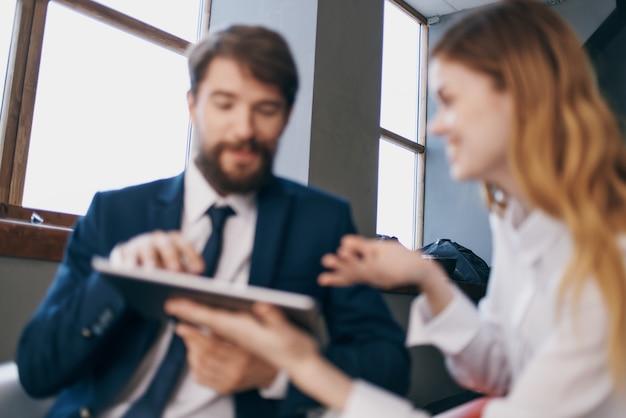 Мужчина и женщина в деловых костюмах работают с планшетом.