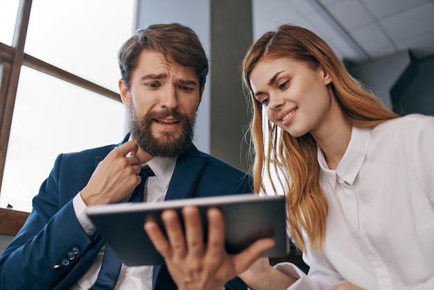 Мужчина и женщина в деловых костюмах работают с офисом планшетных технологий