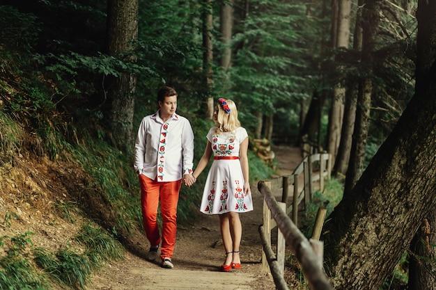 Мужчина и женщина в вышитой одежде проходят по деревянной тропе в лесу