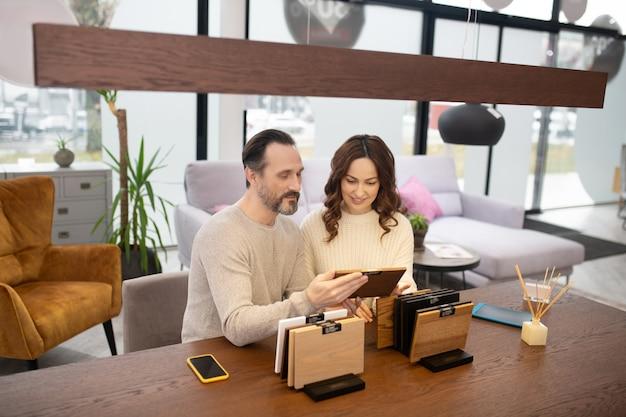 Мужчина и женщина в легких свитерах обсуждают образцы древесины