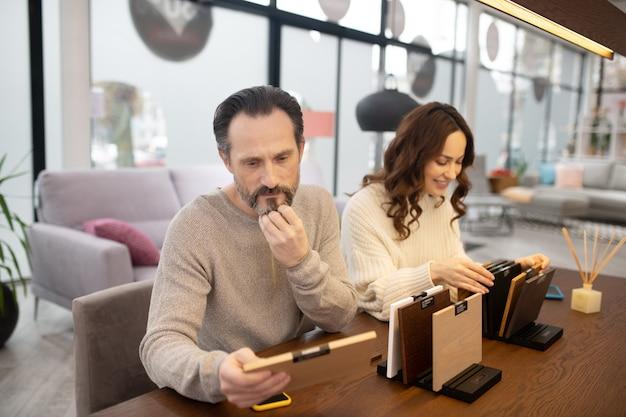 Мужчина и женщина в легких свитерах, глядя на образцы древесины