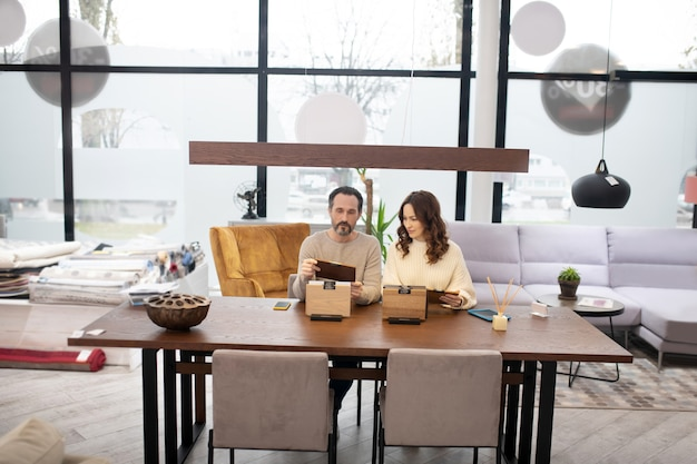 Мужчина и женщина в легких свитерах, сидя за столом в мебельном магазине