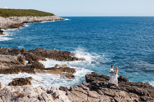 사랑에 빠진 남자와 여자는 바위 해변에서 포용하고 손을 잡고 서있다.