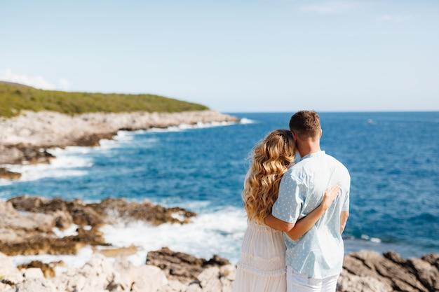 愛の男と女が岩の多い海岸の背面図を抱きしめて立っています