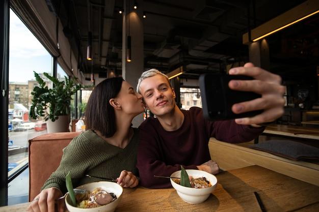 사랑에 빠진 남녀는 공공 장소에서 함께 사진을 찍습니다. 매력적인 갈색 머리 여자가 그녀의 남자 친구 뺨에 키스하는 동안 그는 셀카를 찍기 위해 스마트 폰을 보유하고 있습니다. 소셜 미디어 개념. 레스토랑의 카페.