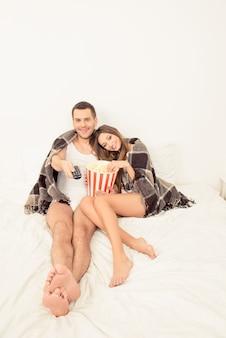Влюбленные мужчина и женщина смотрят фильм с попкорном в постели