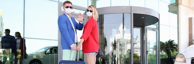 スーツケース付きの医療用マスクの男女がホテルで休むようになりました