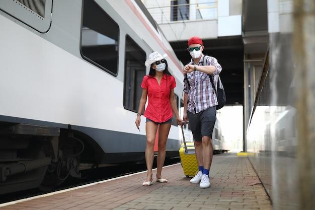 医療用保護マスクを着用した男女がスーツケースを持って電車に沿って歩きます。
