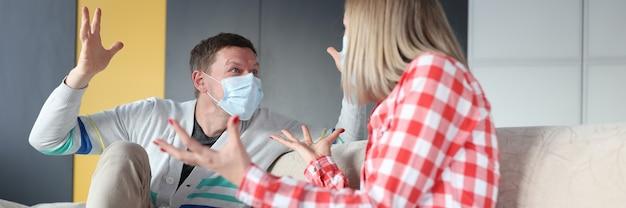 Мужчина и женщина в защитных масках дерутся дома. семейный развод в концепции пандемии коронавируса