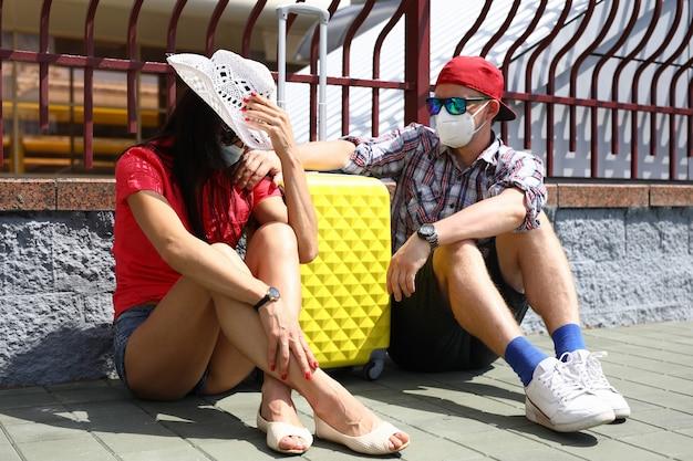 防護マスクの男女がスーツケースを持って駅に座る