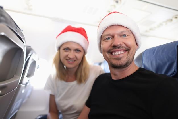 Мужчина и женщина в красных шляпах санта-клауса, летящие в самолете