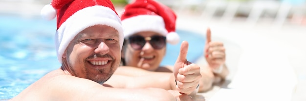 산타클로스 모자를 쓴 남녀가 수영장 옆에서 쉬고 있으며 엄지손가락을 치켜들고 있다