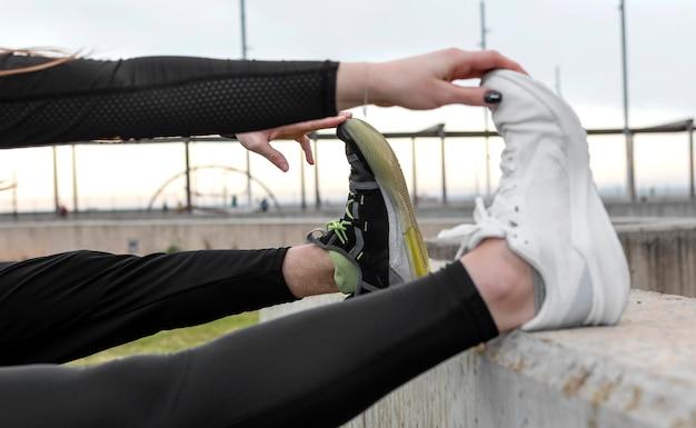 Мужчина и женщина в спортивной одежде, упражнения на открытом воздухе