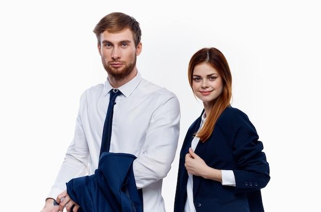 Мужчина и женщина в костюмах стоят рядом с коллегами по работе на светлом фоне финансового офиса. фото высокого качества