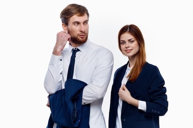 スーツを着た男女が仕事仲間の隣に立つ、オフィスの明るい背景