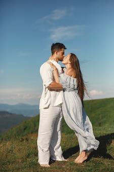 山の中の男と女。日没で恋をしている若いカップル。青いドレスを着た女性。