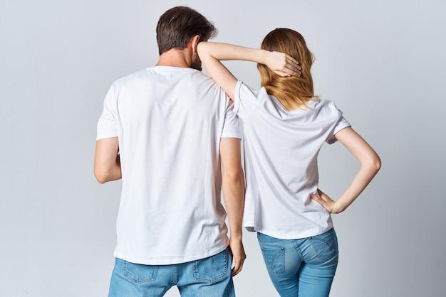 Мужчина и женщина в белых футболках и джинсах создают макет повседневной одежды