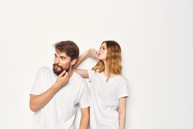 白いtシャツの男性と女性が家族の明るい背景の横に立っています