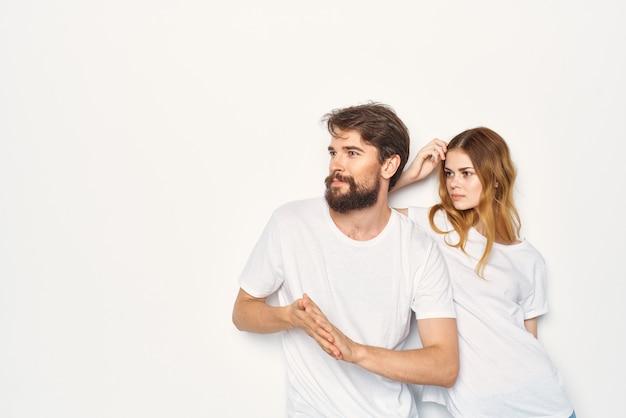 흰색 티셔츠를 입은 남녀가 가족의 밝은 배경 옆에 서 있다