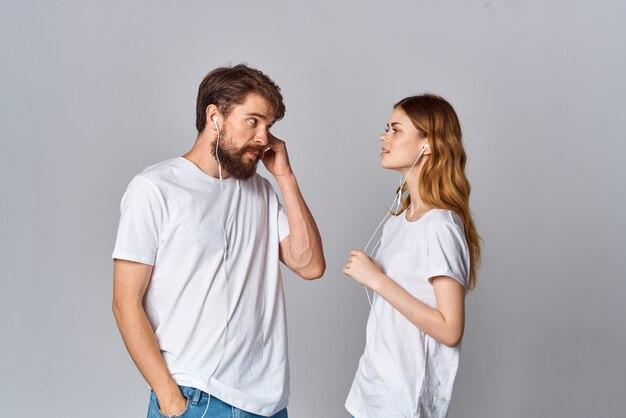 白いtシャツを着た男性と女性がヘッドフォンで友情の音楽の横に立っています