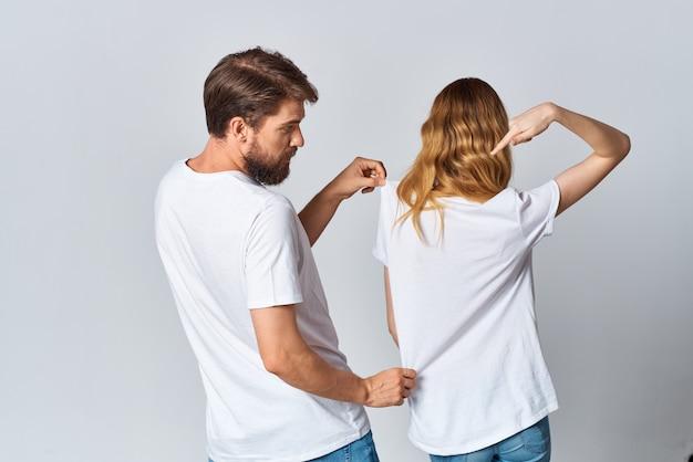 Мужчина и женщина в белых футболках стоят спиной на светлом фоне