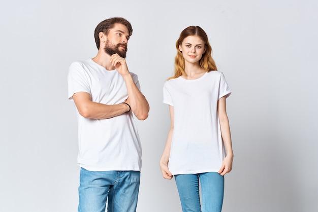 楽しい光の背景をポーズする白いtシャツスタジオファッションの男と女