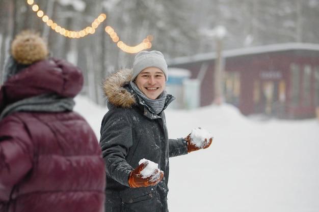 公園で雪の中で遊ぶ冬服の男女