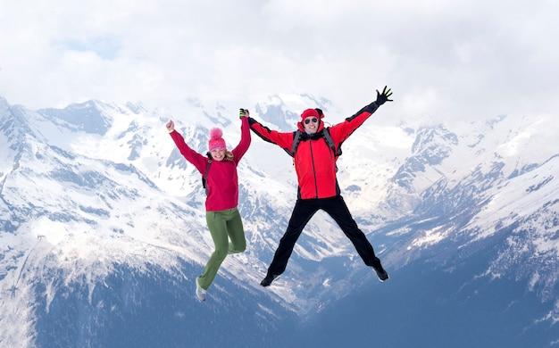 겨울 재킷에 남자와 여자는 눈으로 덮여 산에 손을 잡고 함께 점프