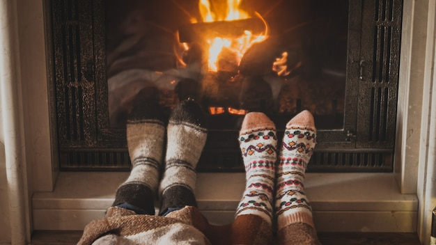 Мужчина и женщина в шерстяных носках греют ноги у горящего камина