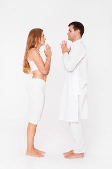 Мужчина и женщина в позе йоги, занятия йогой в паре с тренером